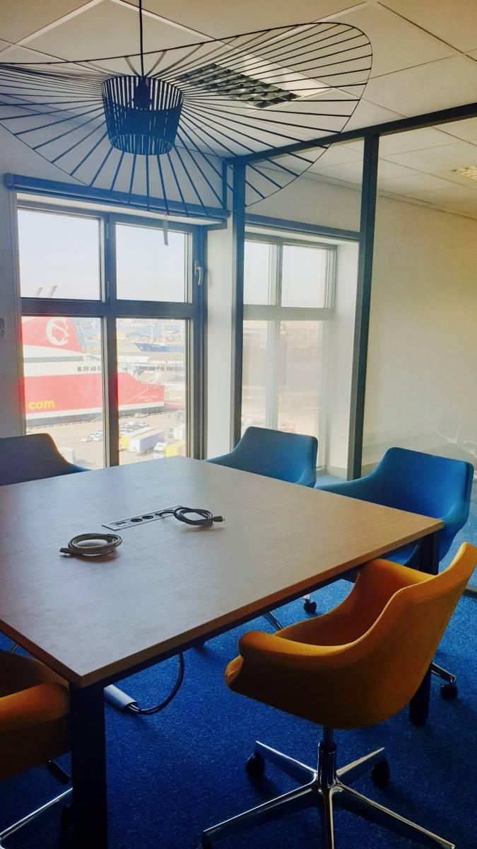 Bulle d'entretien avec table de réunion avec port électrique intégré et fauteuils design sur roulettes de chez NOWYSTYL sur Marseille