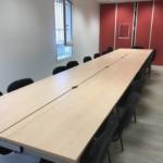 Grande table de réunion avec pieds carrés . Chemin de cable et trappe sur la plan de travail pour faciliter l'accès aux prises.
